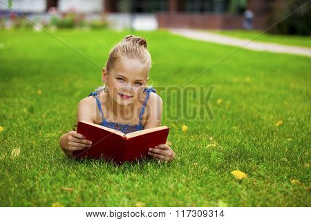Portrait of beautiful happy little girl reading red book lying on green grass in the summer park