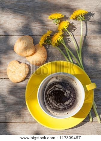 Coffee cup and cookies on garden table. Top view