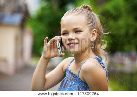 Close up, Little girl talking on cell phone against green of Park in summer