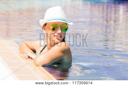Young Woman In White Hat Relaxing In Swimming Pool