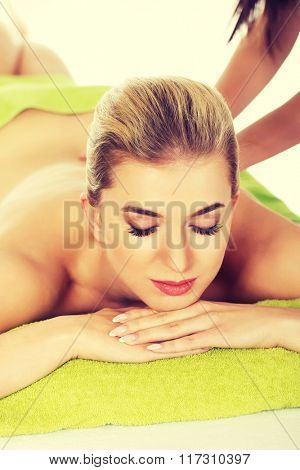 Young relaxed woman lying on a massage table and has massage.
