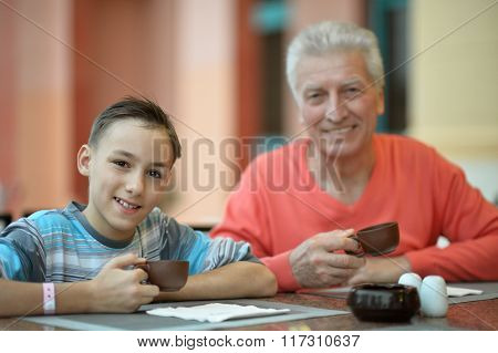 Happy boy with grandfather at breakfast