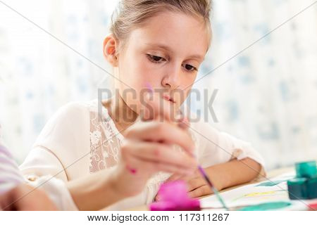 Child painting at easel in the school