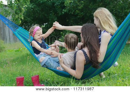 Siblings and cousins family members having fun on blue-green Brazilian hammock in summer garden outd