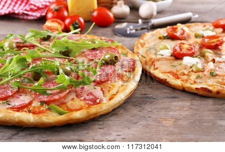 Delicious tasty pizzas with ingredients on table, closeup