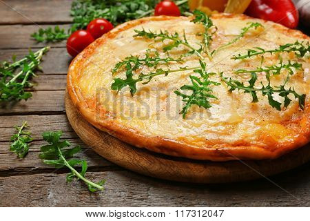 Tasty pizza decorated with herbs and vegetables on wooden background, close up