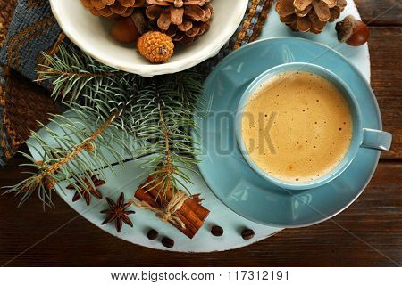 Cup of coffee and Christmas tree branch on wooden mat