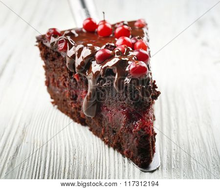 Piece of chocolate cake with cranberries on shovel on wooden table, closeup