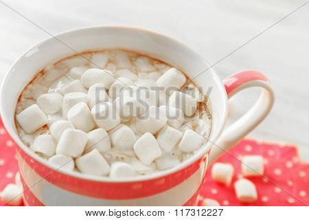 Mug of hot chocolate with marshmallows, on light wooden background