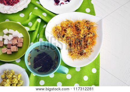 Cup of tea with aromatic dry tea on wooden background
