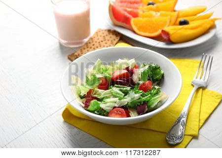 Tasty oatmeal and vegetable salad on wooden background. Healthy eating concept.