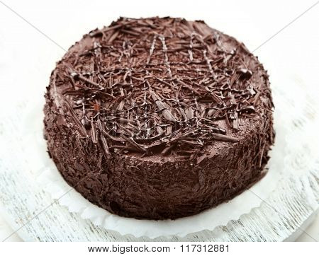 Tasty chocolate cake on wooden table, on light background