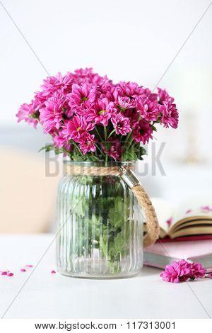 Beautiful flowers in vase on table in room