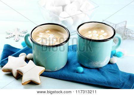 Two mugs of hot cacao with marshmallow, cookies and napkin on blue table