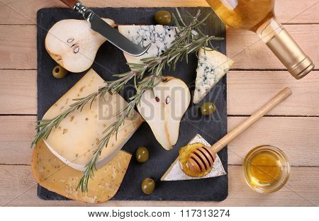Different kinds of cheese with honey on wooden table