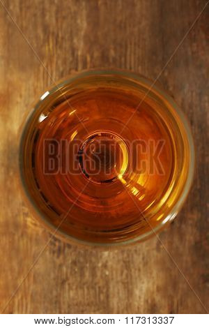 Glass of wine on wooden table. Top view