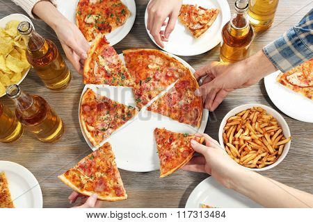 Friendly party with hot pizza and drinks, close up