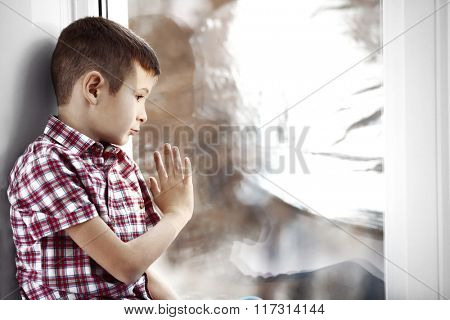 Sad boy sitting near window