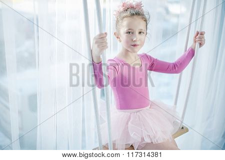 Sad young girl sitting on a swing