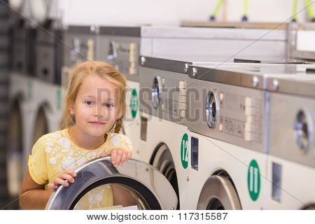 Adorable little girl in laundry room