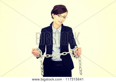 Businesswoman wrapped with metal chain.