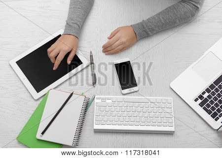 Woman hands at table with computer, tablet, smart phone and other things, top view