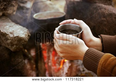 Woman warming hands near the outdoor fire in the nature