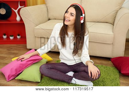 Happy young woman with headphones listening to music on a floor at home