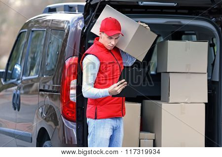 Young handsome delivery man standing near the car with boxes and packages, outdoors