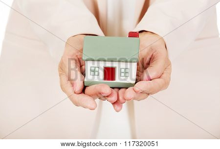 Elderly woman holding house model on open palms