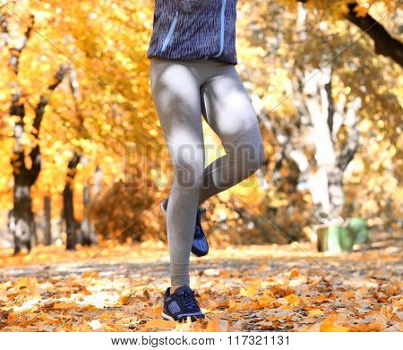 Young  woman jogging in autumn park