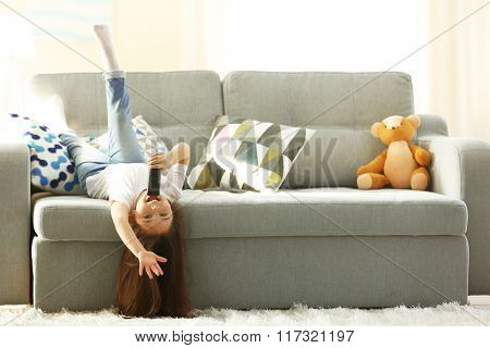 Cute little girl singing in a remote control lying on sofa upside down in the room