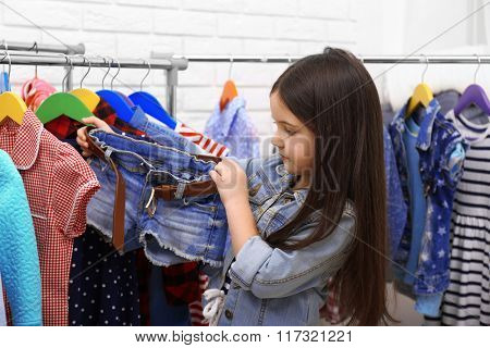 Little girl trying on a new jeans shorts