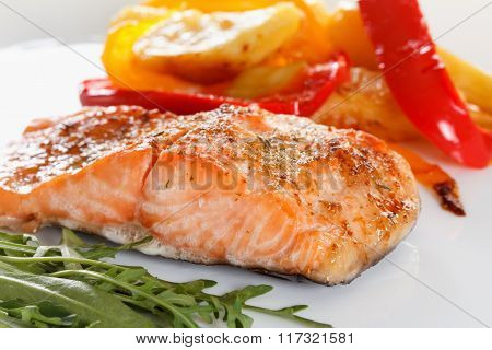 Grilled Salmon Fillet With Vegetables, Spices And Arugula On A Plate