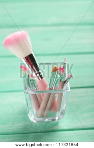 Makeup Brush Set On A Mint Wooden Background