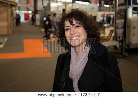 Portrait Of A  Woman Shopper Wearing A Coat- Caucasian Female Seller Looks At Quality Garments Durin