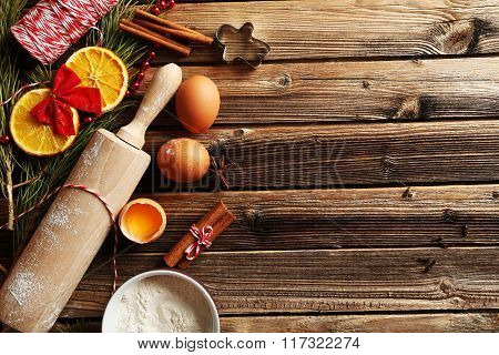 Christmas Tree Branch With Dried Oranges, Cinnamon, Eggs, Flour And Anise Star On Wooden Table