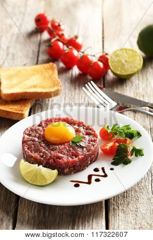 Beef Tartare With Egg Yolk On A Grey Wooden Table