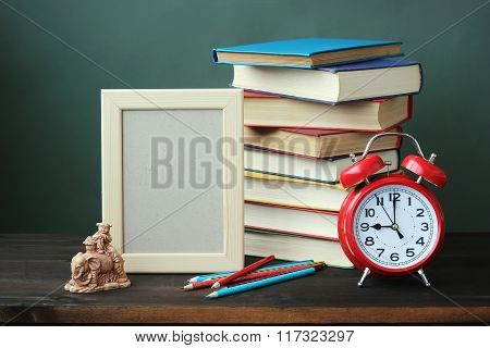 A Still Life With Books, An Alarm Clock And A Frame For A Photo.