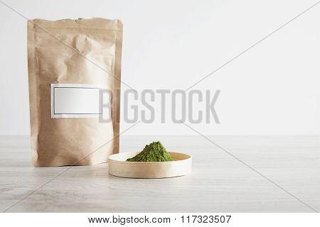 Paper Bag And Matcha Tea On White Table