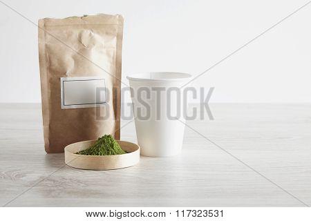 Paper Bag, Glass And Matcha Tea On White Table