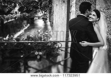 Handsome Groom And Sexy Brunette Bride Hugging On Old Bridge Over River B&w