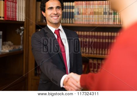 Portrait of a smiling businessman giving an handshake to a customer
