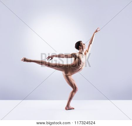 Athletic ballet dancer in a perfect shape performing over the grey background.