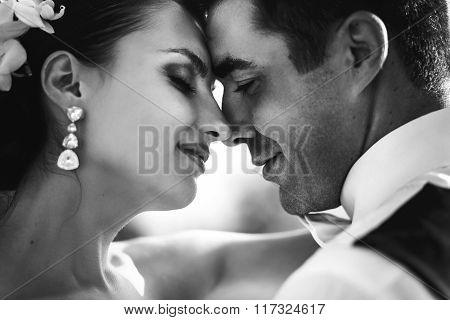 Happy Handsome Groom And Beautiful Bride Hugging On Balcony At Sunset Closeup B&w