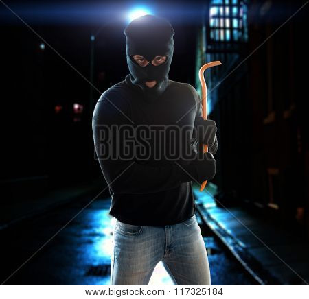 Criminal holding a crowbar in the night