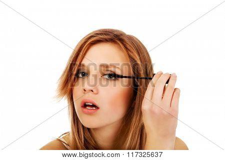 Teenage beautiful woman applying mascara