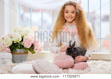 Beautiful little girl sitting on carpet and playing with cute bunny.