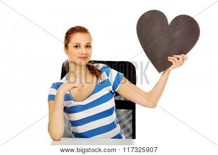 Teenage woman holding black paper heart