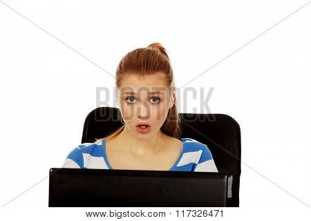 Teenage shocked woman with laptop sitting behind the desk